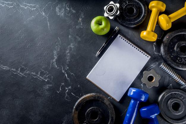 Ferramentas de fitness e halteres com caderno em branco