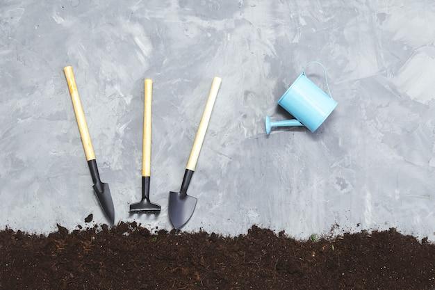 Ferramentas de jardim - enxada, pá, regador e solo em um fundo cinza. conceito de jardinagem e horticultura.