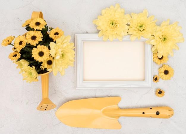 Ferramentas de jardinagem amarelas e flores com moldura de espaço de cópia