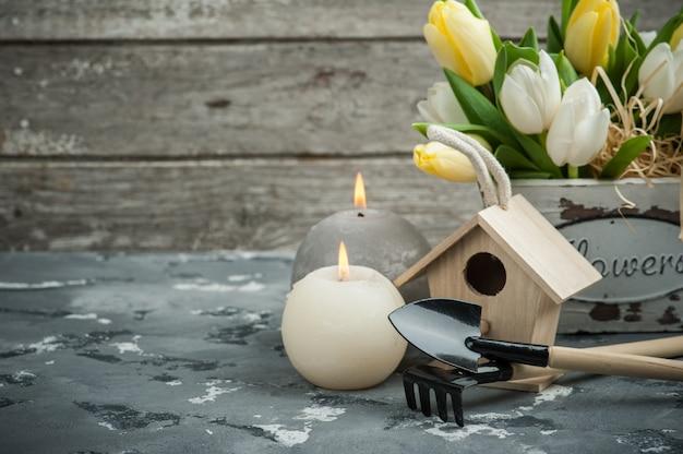 Ferramentas de jardinagem com flores e velas acesas
