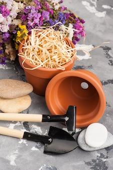 Ferramentas de jardinagem e vasos de barro em terracota