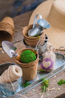 Ferramentas de jardinagem, panelas e utensílios no fundo de madeira rústica