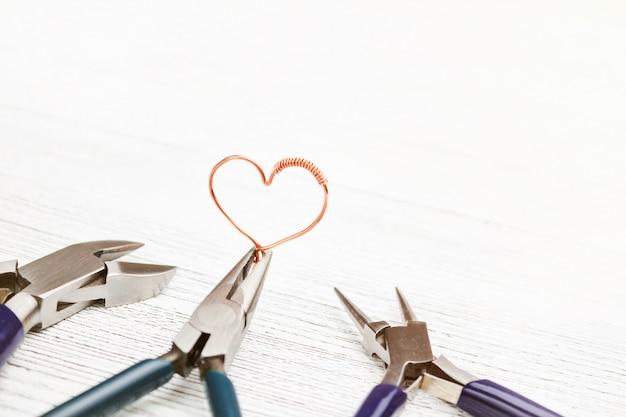 Ferramentas de joias na mesa de madeira branca. coração feito de fio de cobre. fio revestido