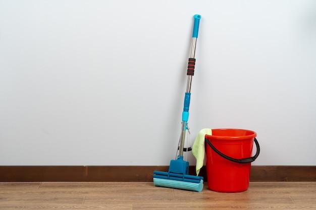 Ferramentas de limpeza para limpeza da casa no piso de madeira