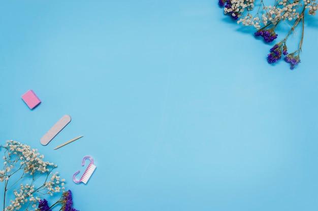 Ferramentas de manicure em um fundo azul são decoradas com flores brancas de gipsófila