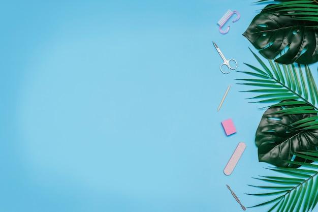 Ferramentas de manicure em um fundo azul são decoradas com folhas verdes de monstera e palmeiras