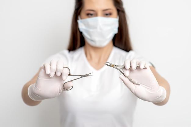 Ferramentas de manicure nas mãos de uma manicure usando máscara branca e luvas