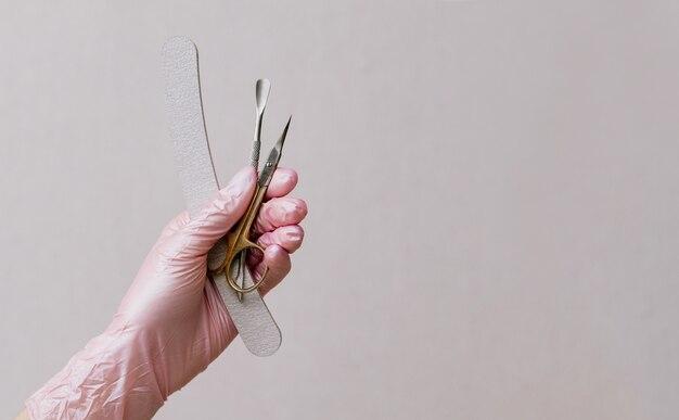 Ferramentas de manicure nas mãos de uma manicure usando máscara e luvas. mulher morena manicure em fundo cinza