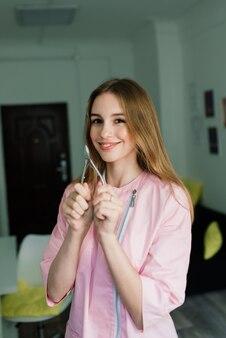 Ferramentas de manicure nas mãos de uma manicure vestindo uniforme rosa em um estúdio