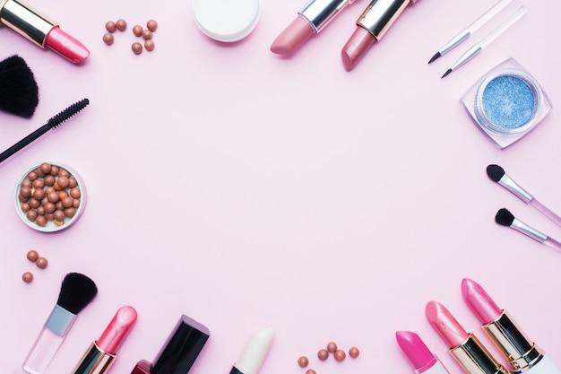 Ferramentas de maquiagem profissional. o batom das escovas blush a sombra para os olhos em um fundo pastel cor-de-rosa com espaço da cópia. lay plana