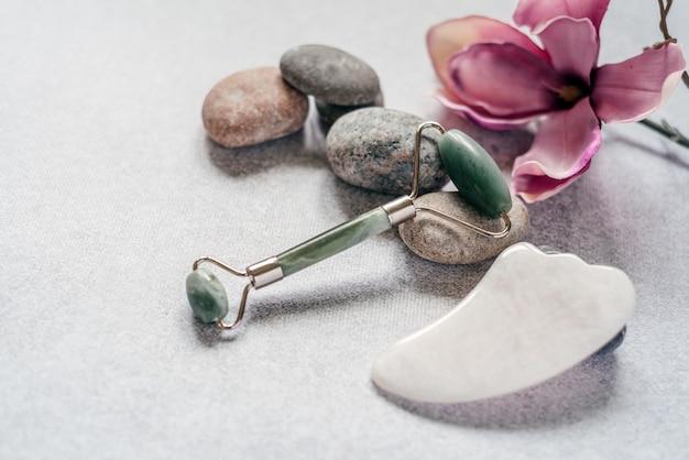 Ferramentas de massagem facial: rolo de massagem jade guasha e raspador com pedras de seixo e flor de magnólia roxa