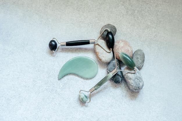 Ferramentas de massagem facial: rolo de massagem jade guasha e raspador com pedras de seixo e folha de monstera tropical