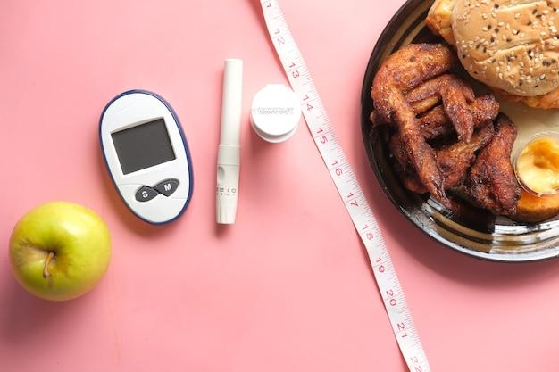 Ferramentas de medição de diabetes e maçã em comparação com junk food
