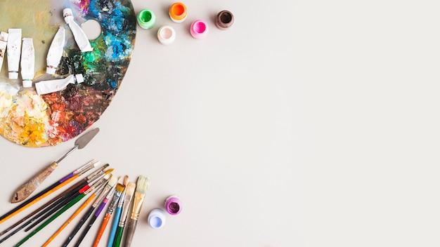 Ferramentas de pintura e pigmentos perto da paleta
