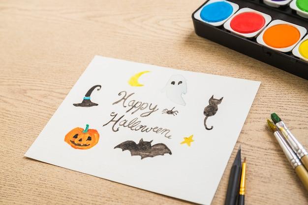 Ferramentas de pintura perto do desenho de halloween