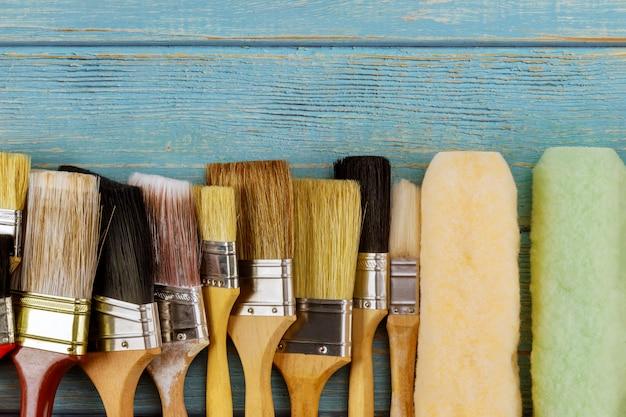 Ferramentas de pintura vários pincéis e rolo na mesa de madeira