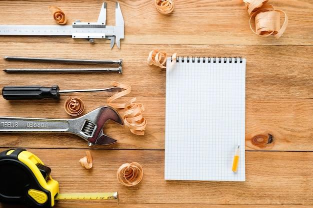 Ferramentas de trabalho e notebook em uma mesa de madeira