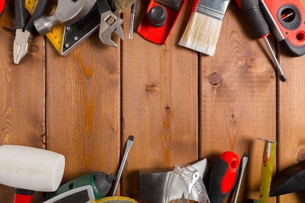 Ferramentas de trabalho sortidas na superfície de madeira
