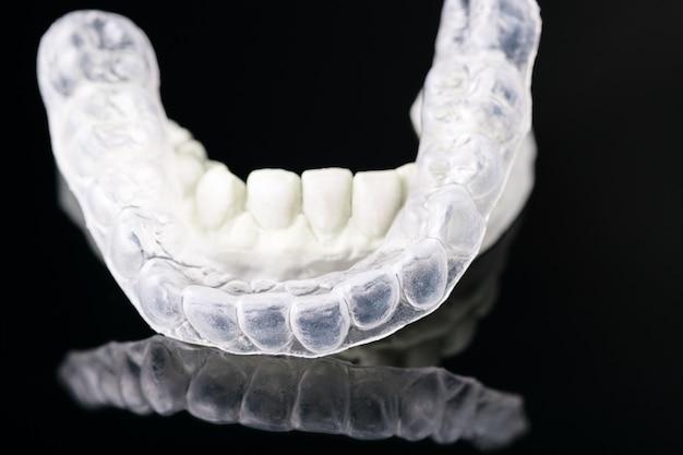Ferramentas dentais e dispositivo ortodôntico do retentor no fundo preto.