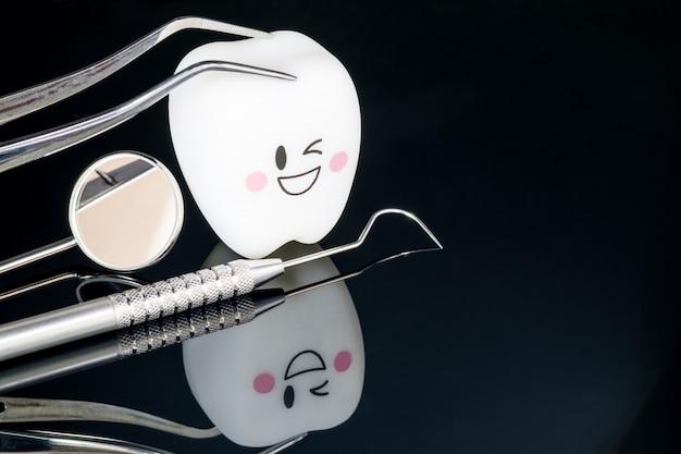 Ferramentas dentais e modelo dos dentes do sorriso no preto.