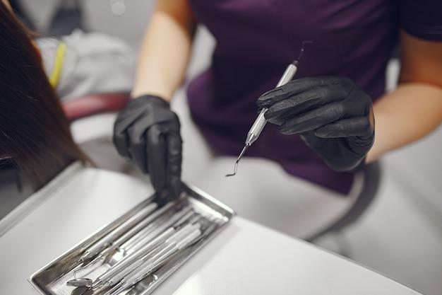 Ferramentas dentais na mão do dentista