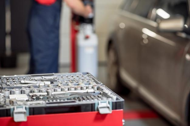 Ferramentas, detalhes. caixa com ferramentas e peças de metal perto do carro e do mecânico de automóveis nos fundos da garagem