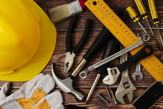 Ferramentas do trabalhador da construção no fundo de madeira da tabela.