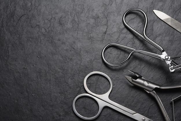 Ferramentas e acessórios de manicure e pedicure em fundo de ardósia preta. copie o espaço