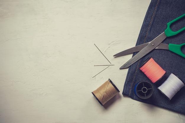 Ferramentas e equipamento sewing no assoalho de madeira branco.