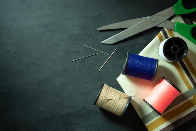 Ferramentas e equipamentos de costura no chão de cimento preto.