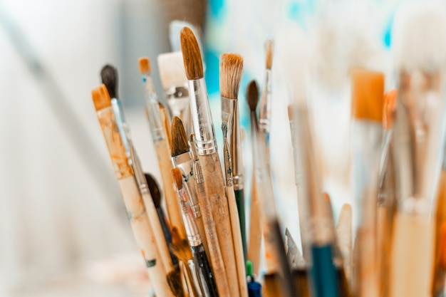Ferramentas e equipamentos para o artista. paleta e pincéis close-up. o processo de desenho e criatividade. a imagem está em azul.