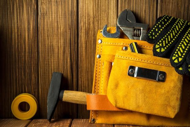 Ferramentas e instrumentos em saco de couro isolado no fundo de madeira.