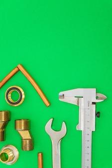 Ferramentas e peças sobressalentes para encanamento isoladas em fundo verde