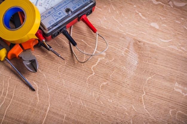 Ferramentas elétricas pinças de testador de resistência de isolamento chave de fenda rolo amarelo fita isolante organizado copyspace na placa de madeira