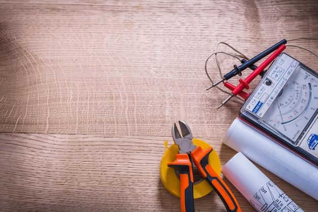 Ferramentas elétricas pinças testador multímetro chave de fenda rolo fita isolante blueprint organizado copyspace na placa de madeira