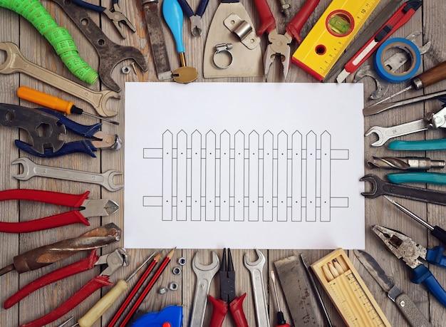 Ferramentas em um assoalho de madeira com um esboço da cerca em uma folha de papel no centro, vista superior.