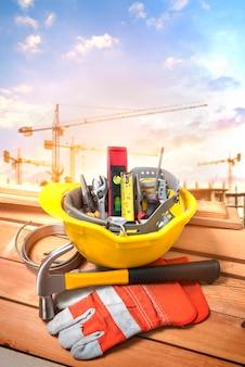 Ferramentas em um capacete amarelo em uma construção com um guindaste de fundo.
