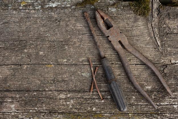 Ferramentas enferrujadas velhas em um espaço de madeira com musgo