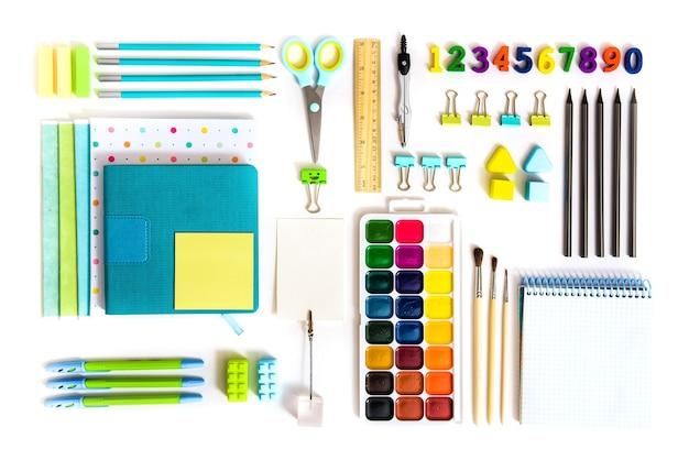Ferramentas escolares em fundo branco. vista de cima. de volta à escola, material escolar - lápis e tintas, régua e borracha, clipes de papel e tesouras, blocos de notas e cadernos.