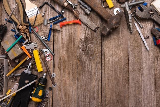 Ferramentas espalhadas do trabalhador em placas de madeira.