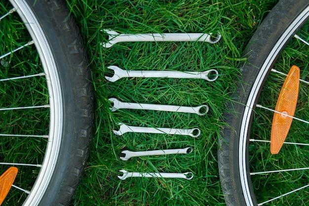 Ferramentas, instrumento para reparar a bicicleta na grama ao ar livre perto de rodas de bicicleta
