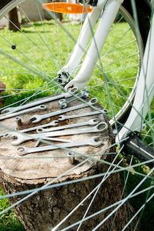 Ferramentas, instrumento para reparar a bicicleta no fundo de madeira ao ar livre perto da bicicleta. reparação de bicicletas.