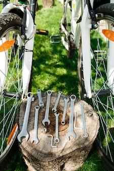 Ferramentas, instrumento para reparar a bicicleta no fundo de madeira ao ar livre perto da bicicleta.