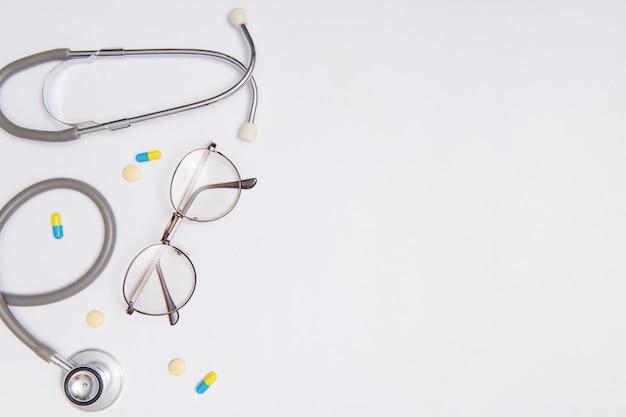 Ferramentas médicas e drogas no conceito de superfície do painel. espaço para design. itens essenciais da vista de cima da mesa para o médico que está tratando e cuidando do paciente no hospital. objeto em papel azul.