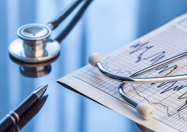 Ferramentas médicas. estetoscópio e eletrocardiograma em uma mesa.