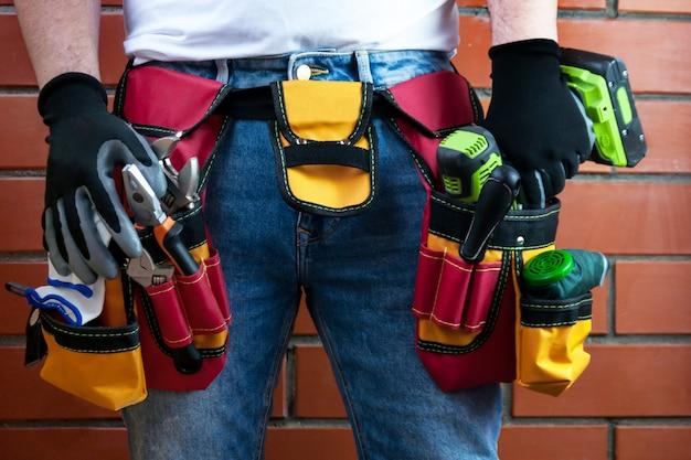 Ferramentas no cinto para ferramentas. o construtor está segurando uma chave de fenda elétrica