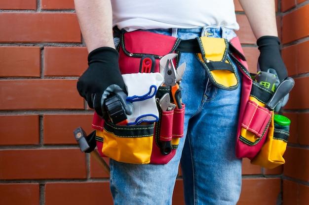 Ferramentas no cinto para ferramentas. o construtor está segurando uma ferramenta.