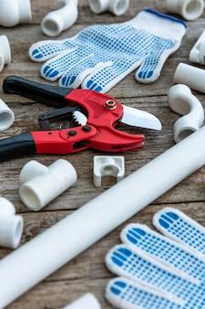Ferramentas para a instalação de tubos de plástico e luvas de trabalho