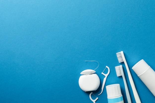 Ferramentas para atendimento odontológico em fundo azul, espaço para texto
