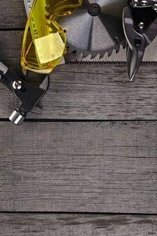 Ferramentas para carpintaria, medição de peças e proteção ocular em superfície de madeira